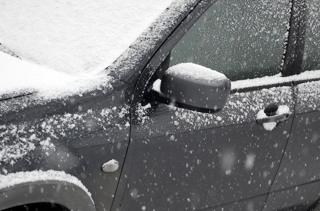 Fragmento del automóvil bajo una capa de nieve después de una fuerte nevada.