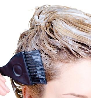 Fragmento de coloración de la cabeza de la mujer con pincel y tinte para el cabello
