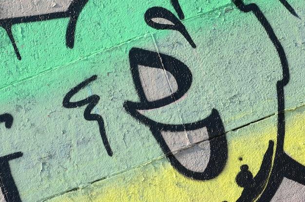 Fragmento de dibujos de graffiti. la antigua muralla decorada con manchas de pintura al estilo de la cultura del arte callejero. textura de fondo de color en tonos verdes
