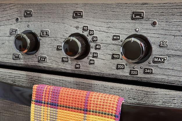 Fragmento del panel frontal de una estufa de gas doméstica con interruptores, una toalla de cocina cuelga del mango