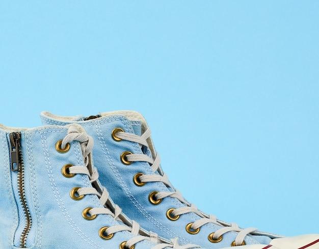 Fragmento de un par de zapatillas textiles desgastadas de color azul claro con cordones y cremalleras