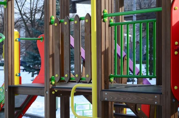 Fragmento de un parque infantil de plástico y madera, pintado en diferentes colores.