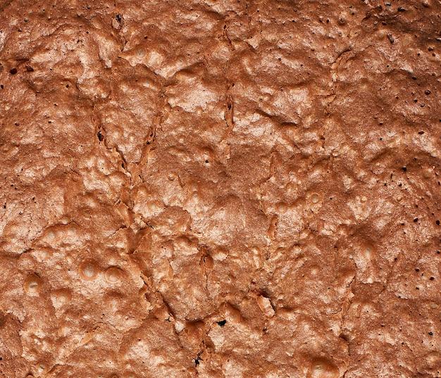 Fragmento de pastel de chocolate brownie horneado con fondo de superficie agrietada