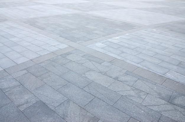Fragmento de la plaza pavimentada de un gran granito de baldosas.