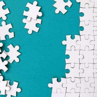 Fragmento de un rompecabezas blanco doblado y una pila de elementos de rompecabezas sin combinar sobre el fondo de una superficie azul.