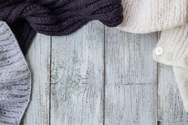 Fragmento de ropa de tejer en el fondo de madera blanco