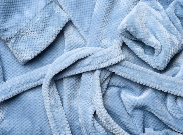 Un fragmento de una túnica de felpa azul grisácea con un cinturón, de cerca