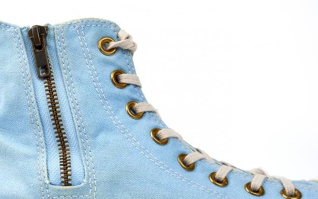 Fragmento de una zapatilla azul con cordones textiles blancos y un cierre de cremallera de hierro.
