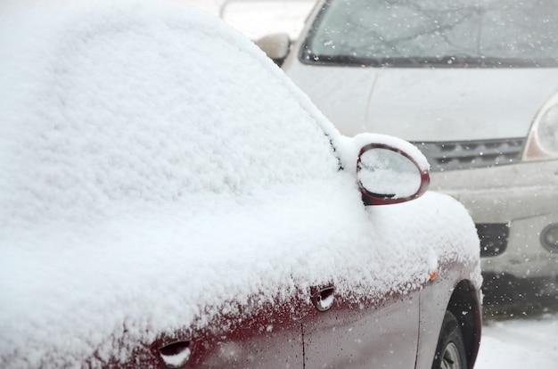 Fragmentos de coches aparcados cubiertos de nieve.