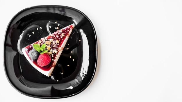 Frambuesa y menta con tarta de queso en un plato negro sobre fondo blanco