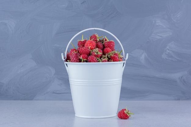 Frambuesas apiladas en un balde blanco sobre fondo de mármol. foto de alta calidad