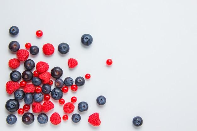 Frambuesas con arándanos, grosellas rojas vista superior sobre un fondo blanco.
