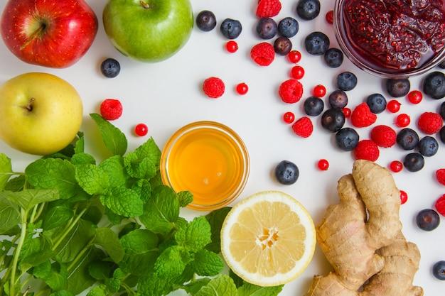 Frambuesas con miel, manzanas, arándanos, grosellas rojas, limón, jengibre, hojas de menta vista superior sobre una superficie blanca