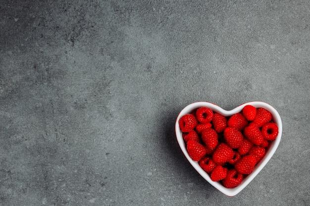 Frambuesas en un recipiente en forma de corazón sobre un fondo gris con textura. vista superior. espacio para texto