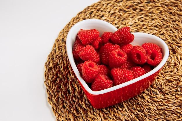 Frambuesas rojas en un plato en forma de corazón alto ángulo de visión sobre un mantel de mimbre y fondo blanco.