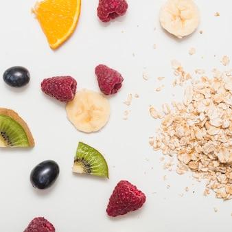 Frambuesas; uvas; plátano; rodajas de kiwi y naranja con lagos de avena sobre fondo blanco