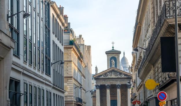 Francia. día de verano en parís. catedral con columnas al final de una calle estrecha