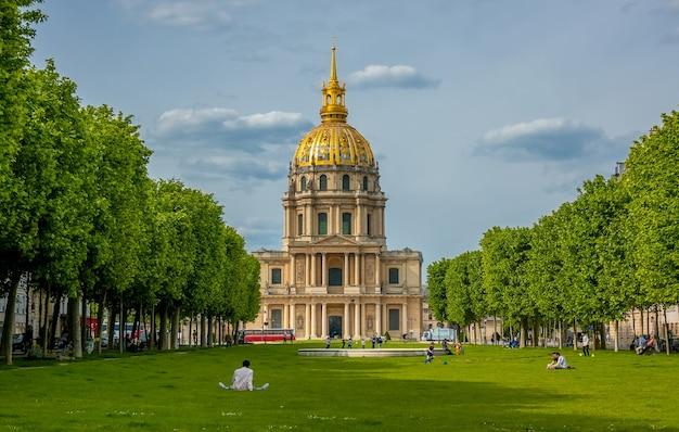 Francia, paris. capilla de saint louis des invalides (lugar del funeral de napoleón) y césped verde con gente descansando