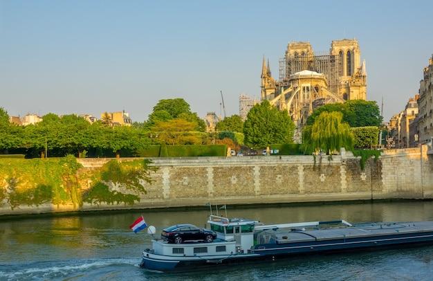 Francia. parís. mañana soleada de verano en el terraplén del sena. notre dame en andamios después de un incendio en 2019. barcaza en el río