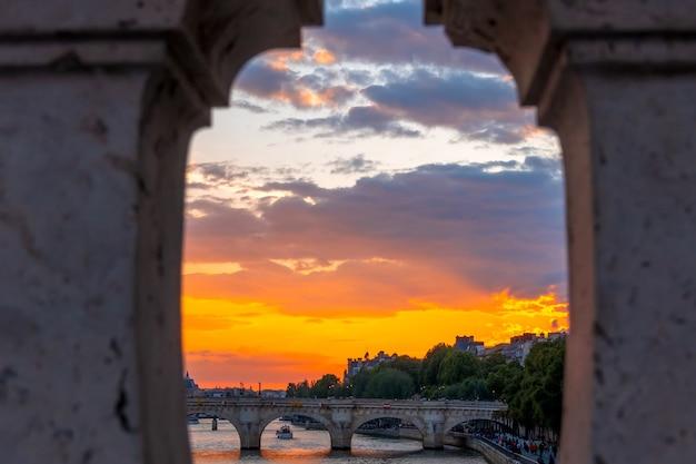 Francia. puesta de sol de verano sobre el río sena en parís. ver a través de la valla de granito del puente.