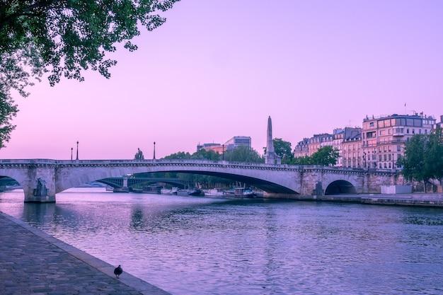 Francia. temprano en la mañana en verano en parís. terraplén del río sena y puentes y barcazas en la orilla