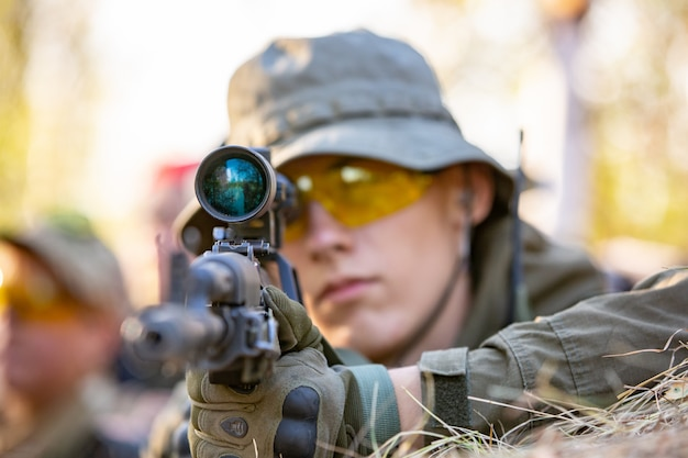 Francotirador armado con gran calibre, rifle de francotirador, disparando a objetivos enemigos al alcance del refugio, sentado en una emboscada