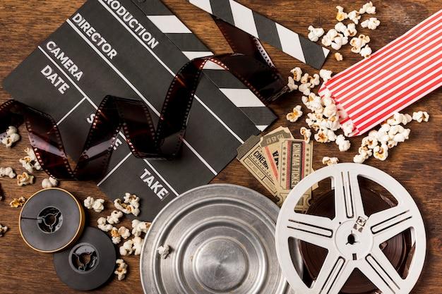 Franjas negativas con claqueta; carretes de película; boletos y palomitas en mesa de madera.