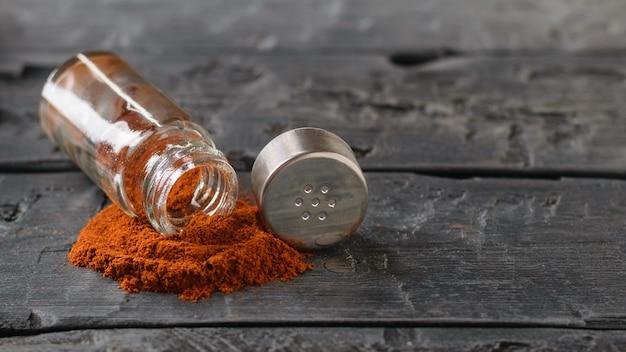 Un frasco abierto de pimiento rojo en polvo sobre una mesa vintage