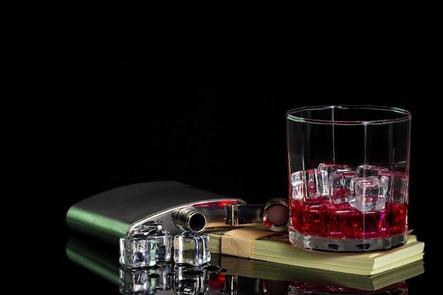 Frasco de acero inoxidable, alcohol y hielo en mesa con vidrio en billete de dólar