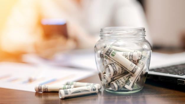 Un frasco con billetes enrollados sobre la mesa. laptop, papeles, mujer en el fondo