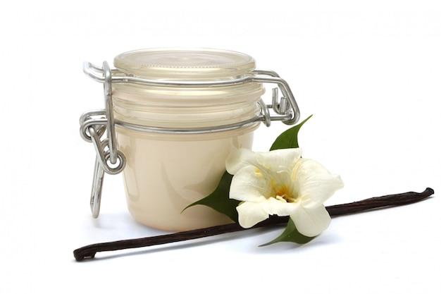 Frasco cerrado con una sustancia cremosa blanca, flor blanca y vainilla en barra sobre blanco