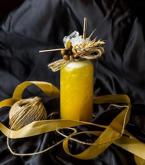 Un frasco de cóctel amarillo decorado con hierbas secas e hilos en la parte superior.