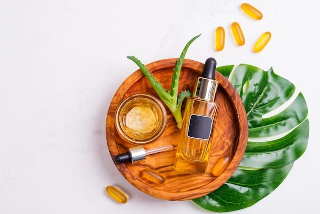 Frasco cosmético con aceite o ácido hialurónico y frasco con máscara para la cara, cápsulas de gel omega 3 en placa de madera, aloe vera y hoja de palma y una toalla blanca.