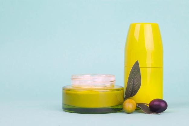 Frasco con crema con extracto de oliva sobre fondo verde lima.