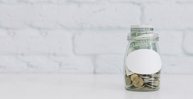 Frasco de vidrio lleno de monedas y nota de la moneda en el escritorio contra la pared de ladrillo