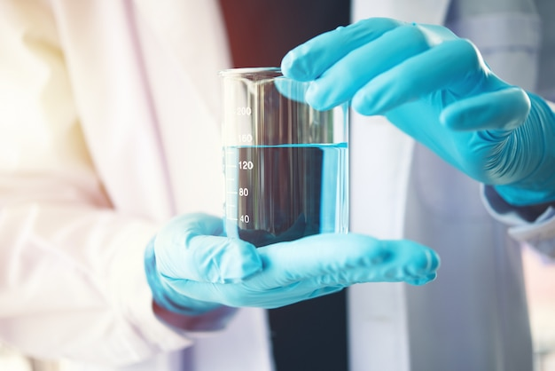 Frasco en mano científica con tubo de ensayo en rack