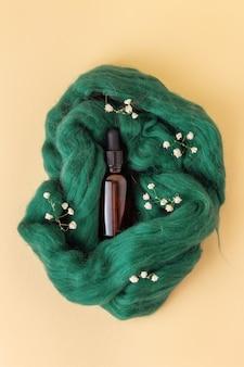 Frasco pequeño con aceite esencial o suero sobre lana verde con gypsophila. vial de vidrio con pipeta y tapa negra.