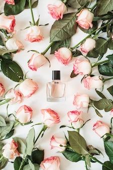 Frasco de perfume de mujer plano laico en marco de flores rosas sobre superficie blanca
