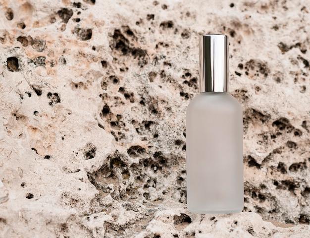 Frasco de perfume de vista superior en arreglo de rocas