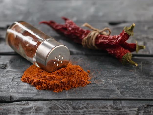 Un frasco de pimiento rojo desde las vainas hasta la mesa rústica.