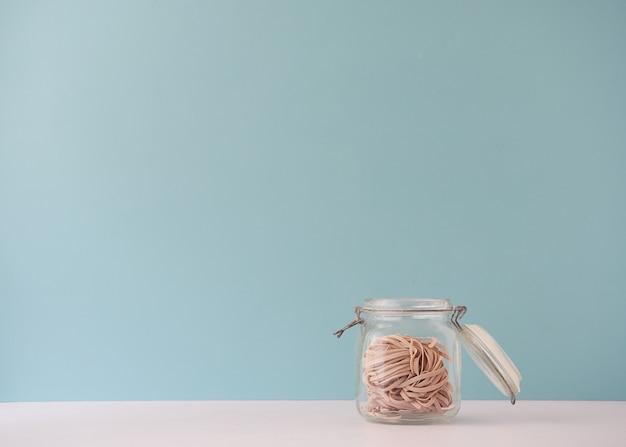 Frasco de vidrio abierto con pasta nido de tagliatelle de trigo integral. vista frontal con espacio de copia