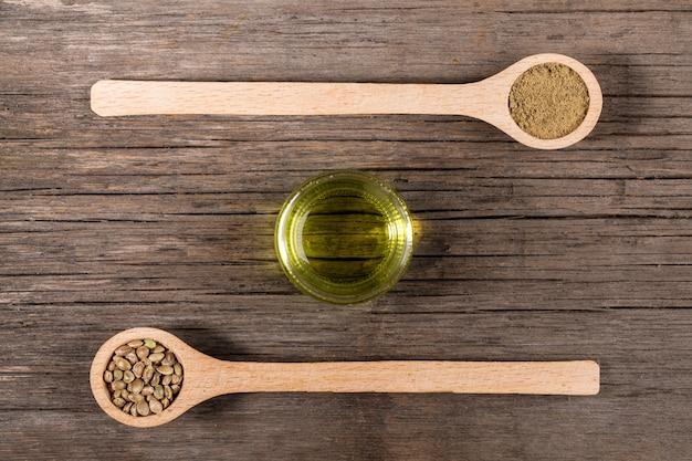 Frasco de vidrio con aceite de cáñamo y dos cucharas de madera con granos de cannabis y harina en tableros de madera viejos.