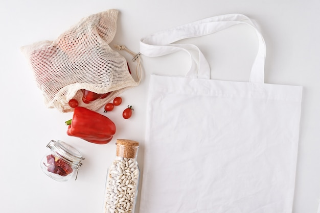 Frasco de vidrio y bolsa de compras con verduras frescas