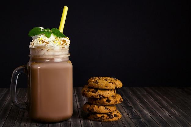 Frasco de vidrio con cacao o chocolate caliente, paja, galletas con una miga de chocolate, crema batida y una rama de menta