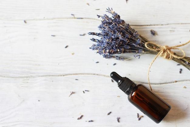 Frasco de vidrio con cosmética orgánica con un ramo de lavanda. concepto de belleza de blogs