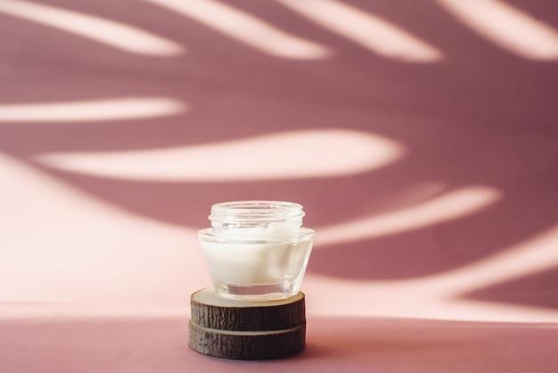 El frasco de vidrio con crema hidratante blanca sobre sierra de madera corta sobre un fondo rosa. loción en el fondo de la sombra tropical de una hoja de palma. el concepto de cuidado de la piel.