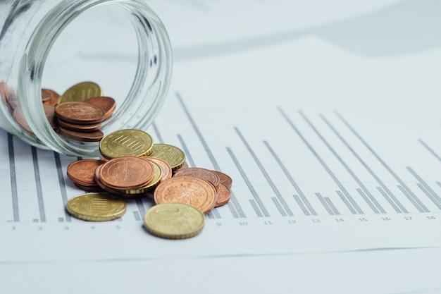 Frasco de vidrio con dinero, monedas derramadas desde una alcancía sobre fondo de gráficos gráficos