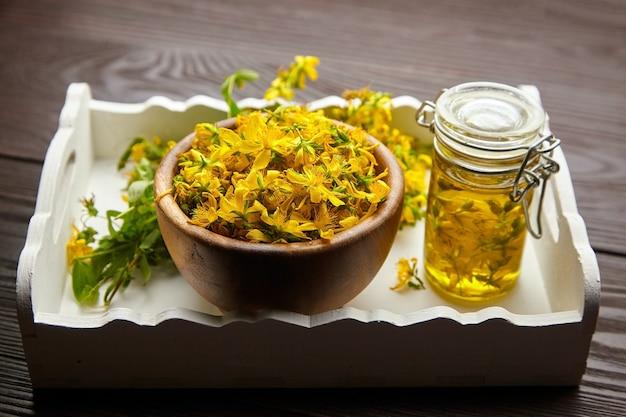 Frasco de vidrio con extracto de aceite de hipérico o hierba de san juan y cuenco de madera con flores frescas en bandeja de madera blanca