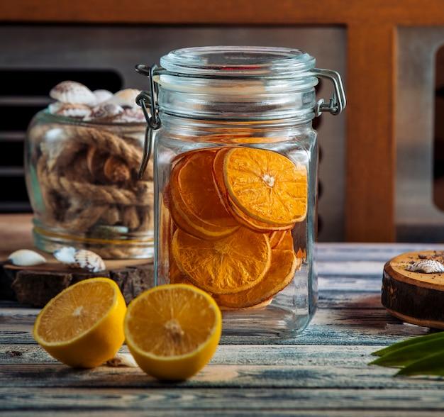 Frasco de vidrio hermético con rodajas de naranja seca