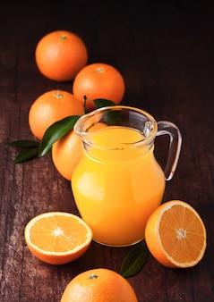 Frasco de vidrio de jugo de naranja fresco orgánico con naranjas crudas sobre fondo de madera oscura